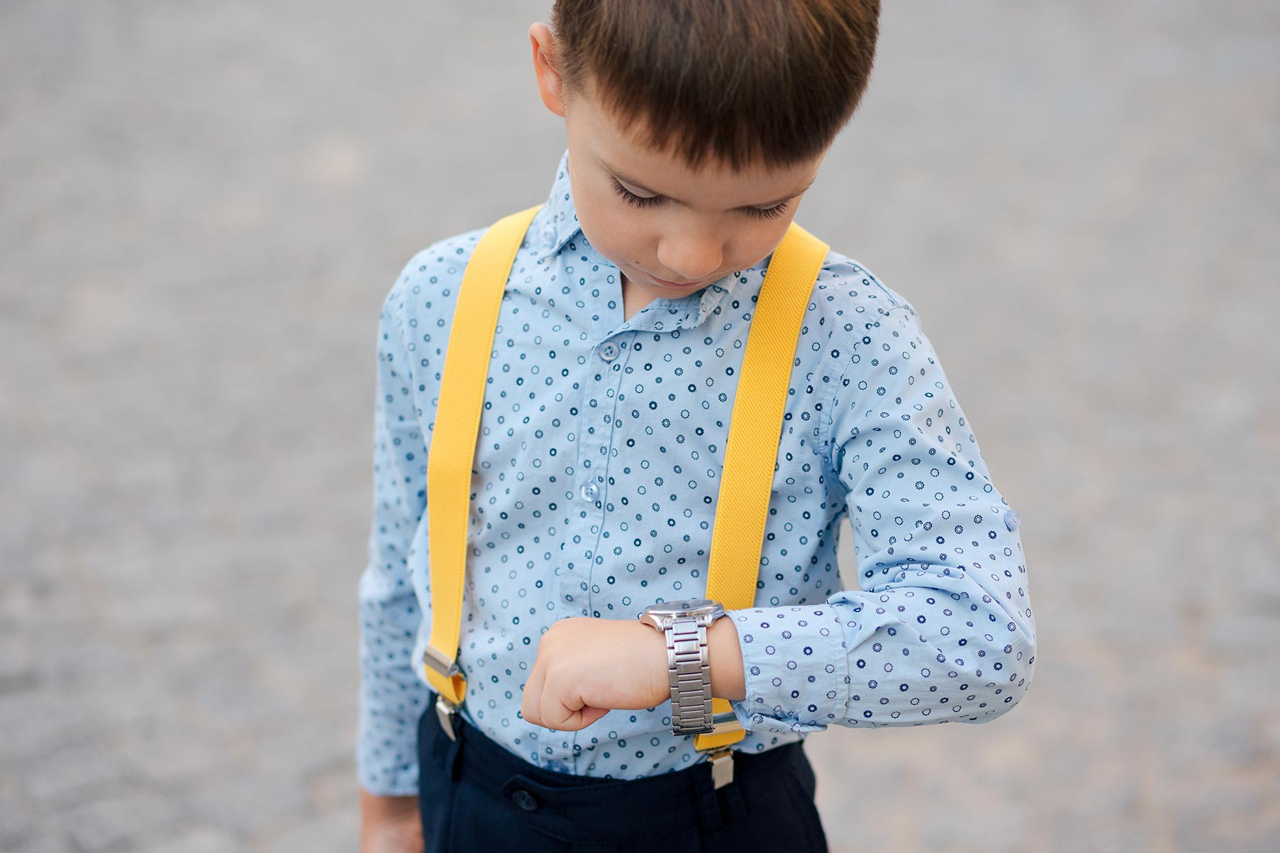 boy-verifying-time-on-his-silver-watch-on-his-hand-Y348Y5G.jpg